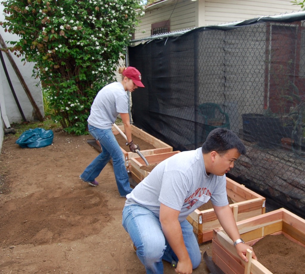 Erin Buss '09 and Brian Tsu '00 load up the plant beds.